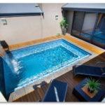 kolam renang belakang rumah dengan air terjun