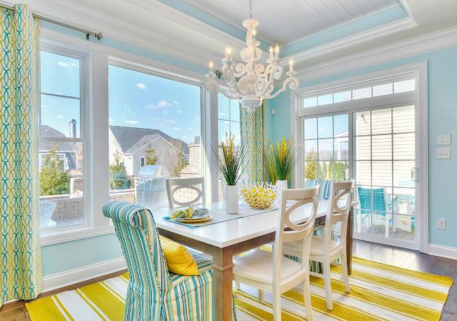ruang makan menghadap luar jendela terang warna tosca dengan kuning karpet